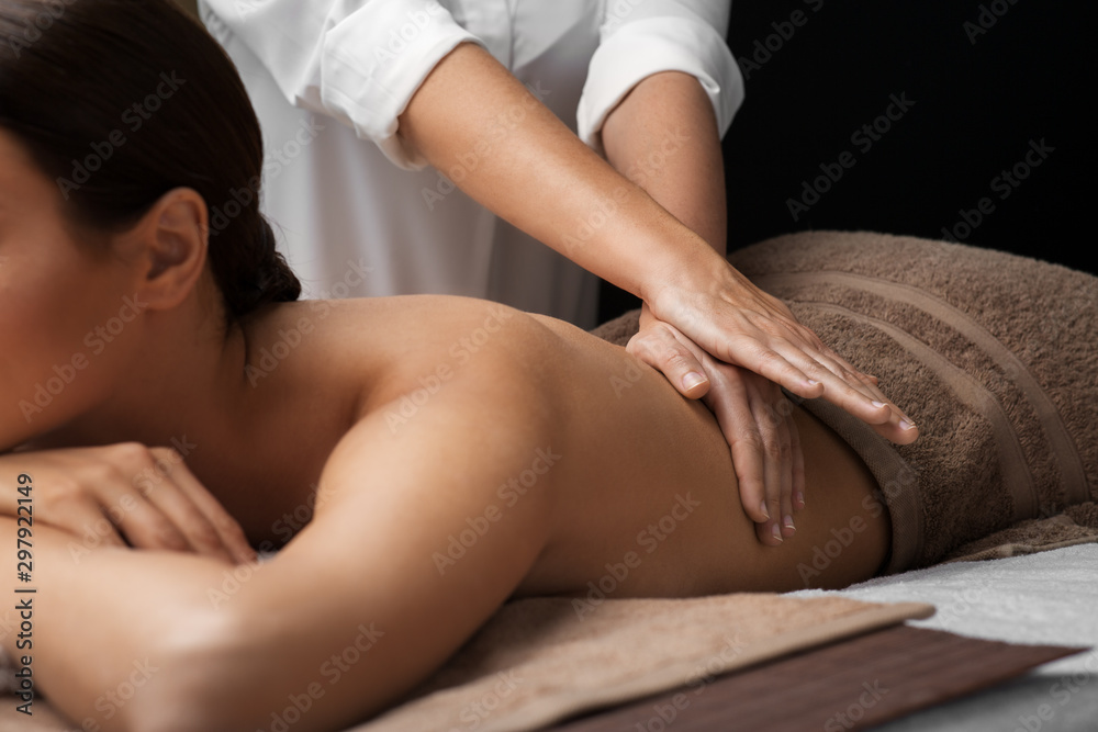 Fototapeta wellness, beauty and relaxation concept - beautiful young woman lying and having back massage at spa