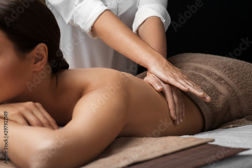fototapeta na szkło wellness, beauty and relaxation concept - beautiful young woman lying and having back massage at spa