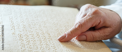 Photo woman reading braille text on old book