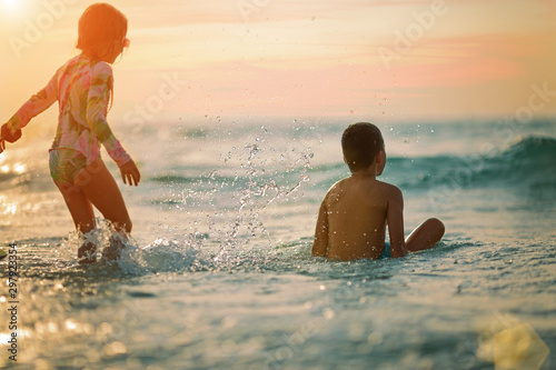 sister and brother on the beach at sunset, rear view - 297923354