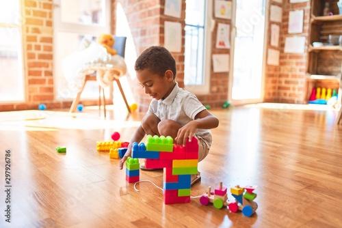 Obraz Beautiful african american toddler playing with building blocks smiling at kindergarten - fototapety do salonu