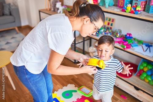 Pinturas sobre lienzo  Beautiful teacher and toddler using alarm clock at kindergarden