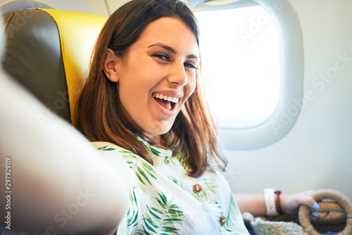 Obraz na plátne  Young traveller woman sitting inside plane at the airport with sky view from the