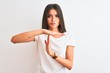 Leinwandbild Motiv Young beautiful woman wearing casual t-shirt standing over isolated white background Doing time out gesture with hands, frustrated and serious face