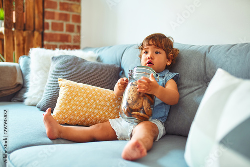 Fotografia Beautiful toddler child girl holding jar of cookies sitting on the sofa