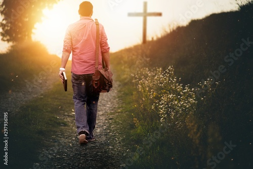 Obraz na plátně Male holding the bible walking up to the hill towards the cross with a blurred b