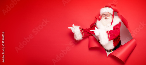 Santa Claus pointing on red empty background. - 297940536