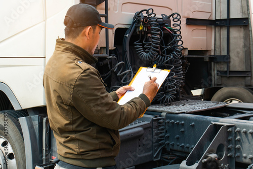 Obraz Truck driver inspecting safety daily checklist to before driving the truck - fototapety do salonu