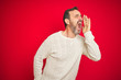 canvas print picture - Handsome middle age senior man with grey hair over isolated red background shouting and screaming loud to side with hand on mouth. Communication concept.
