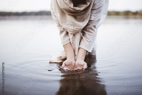 Canvas-taulu Closeup shot of a female wearing a biblical robe standing in the water while was