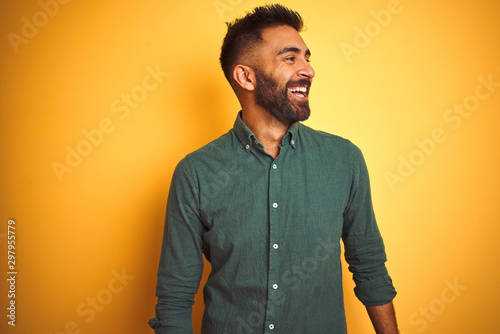 Fotografia  Young indian businessman wearing elegant shirt standing over isolated white background looking away to side with smile on face, natural expression