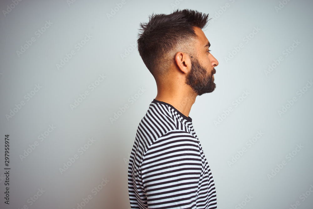Fototapeta Young indian man wearing black striped t-shirt standing over isolated white background looking to side, relax profile pose with natural face with confident smile.