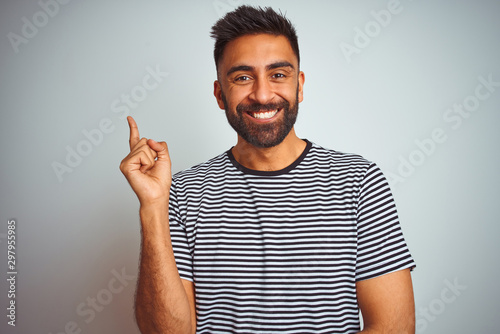 Fotografia  Young indian man wearing black striped t-shirt standing over isolated white background with a big smile on face, pointing with hand and finger to the side looking at the camera