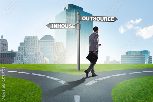 Pinturas sobre lienzo  Businessman at crossroads deciding between outsourcing and inhou