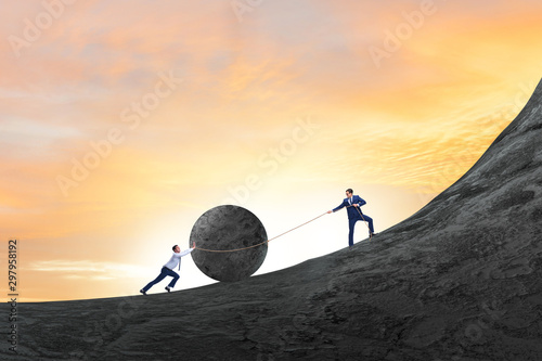 Obraz na plátně  Teamwork example with business people pushing stone to top