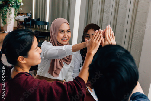 Group of multicultural Asian ladies smiling and doing high five after finishing Wallpaper Mural