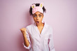 Young african american woman wearing pajama and mask over isolated pink background Surprised pointing with hand finger to the side, open mouth amazed expression.