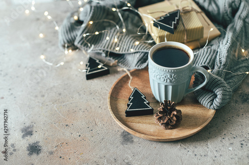Foto auf Leinwand Kaffee Christmas background with mug of hot coffee, cozy sweater, garland lights, gifts and festive decoration. Copy space for text. Cozy mood holiday card concept.