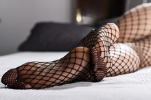 Female Feet On The Bed Close-up. Legs Of A Girl In Tights In A Net. A Woman In Stockings Lies On A Sofa.