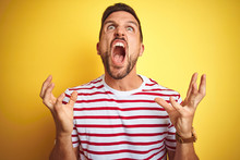Young Handsome Man Wearing Casual Red Striped T-shirt Over Yellow Isolated Background Crazy And Mad Shouting And Yelling With Aggressive Expression And Arms Raised. Frustration Concept.
