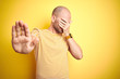 Leinwanddruck Bild - Young bald man with beard wearing casual striped t-shirt over yellow isolated background covering eyes with hands and doing stop gesture with sad and fear expression. Embarrassed and negative concept.