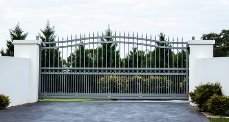 Grey metal wrought iron driveway property entrance gates set in white concrete brick fence, garden trees in background