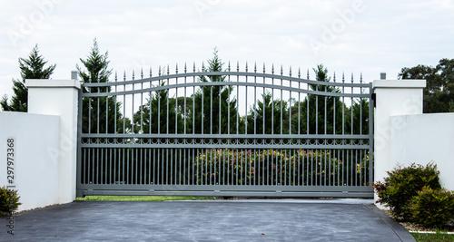 Fotomural Grey metal wrought iron driveway property entrance gates set in white concrete b