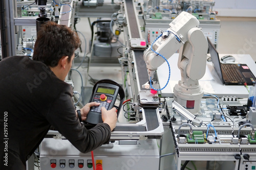 Fototapeta Man is holding teach panel to control a robotic arm which is integrated on smart factory production line. industry 4.0 automation line which is equipped with sensors and robotic arm. Selective Focus. obraz