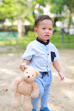 Funny Face Asian Little Boy Walking With Teddy Bear At Garden Outdoor.