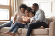 Happy black family with kids relax on sofa with tablet