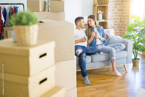 Fotografía  Young couple moving to a new home relaxing sitting on the sofa while drinking a