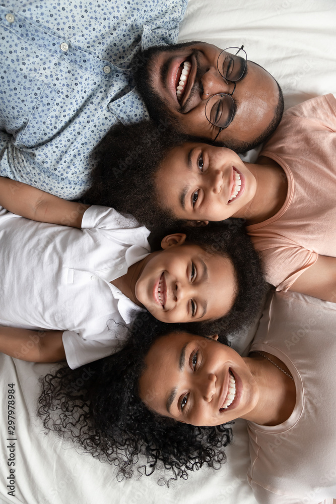 Fototapety, obrazy: Top view portrait of smiling black family lying on bed