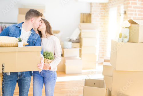 Fotografiet  Beautiful young couple smiling in love holding cardboard boxes, happy for moving