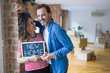 Middle age senior couple moving to a new house, smiling happy in love with apartmant holding a blackboard with new home text