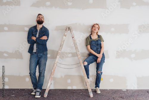 Young couple take a break to admire renovations Wallpaper Mural