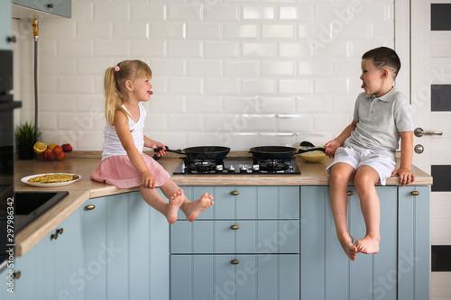 Fototapeta siblings children fry pancakes in the kitchen