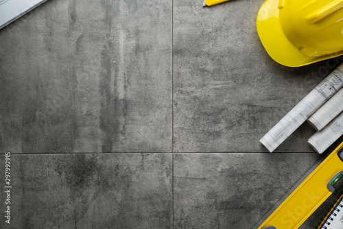 Fototapeta Contractor concept. Yellow hardhat, libella and plans on the gray tiles. obraz na płótnie
