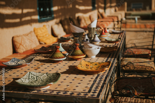 Moroccan meal table settings with ceramic tajines and dishes. Canvas Print