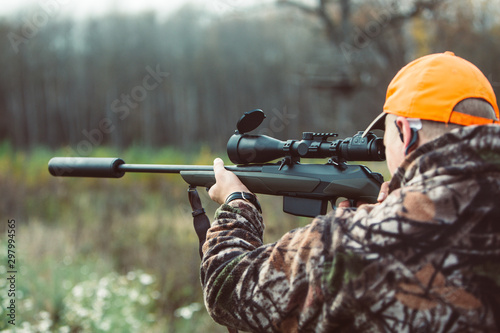 Leinwand Poster Hunter hold rifle  and aiming to deer