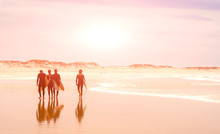 A Group Of Surfers Walks Along...