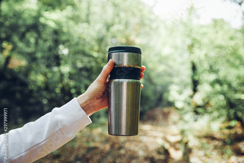 Fotografía  Unrecognizable woman traveler holding thermos mug on background of green forest