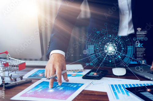 Business report, analysis and planning, Businessman hand pointing at business document and a tablet, mobile phone displaying financial data with icon network connection background Fototapete