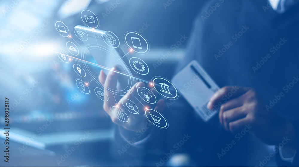 Fototapeta Businessman with mobile smartphone and credit card in hand paying online and shopping on virtual interface global network, online banking and digital marketing.