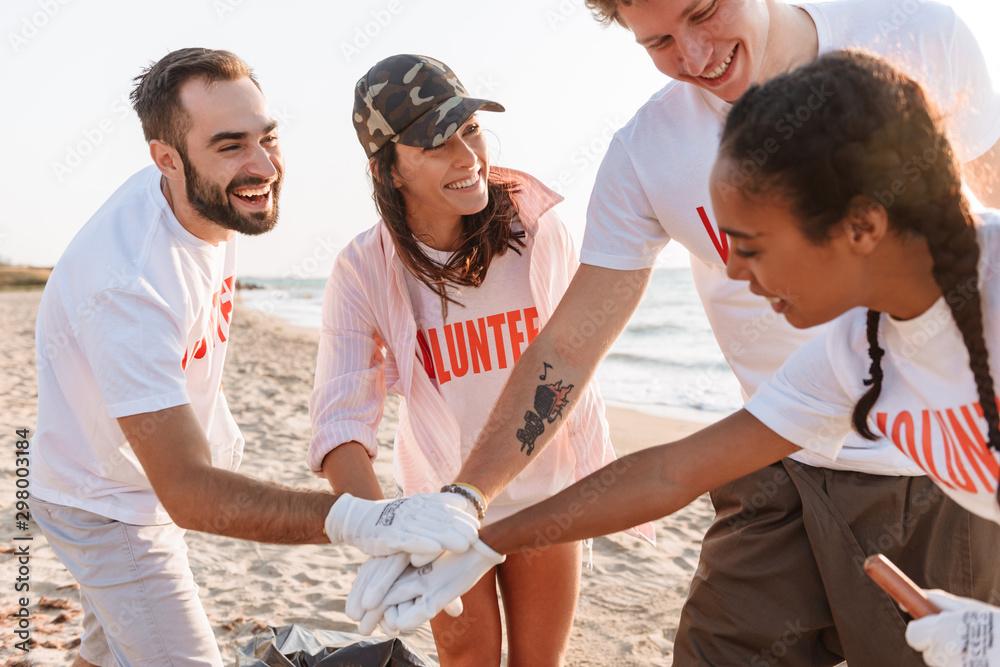 Fototapeta Image of smiling teamwork volunteers holding hands together