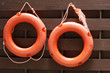 Orange lifebuoys hanging on a wooden wall. Safety on a water, life ring on a beach