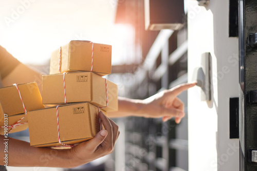 Fényképezés Delivery man holding parcel boxes and ring the doorbell on the client's door in the morning background