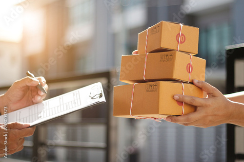 Fotografía  Delivery man holding parcel boxes while a man is signing documents in morning ba