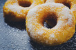 Bakery sweet donuts sprinkled with sugar powder on white plate on black table background