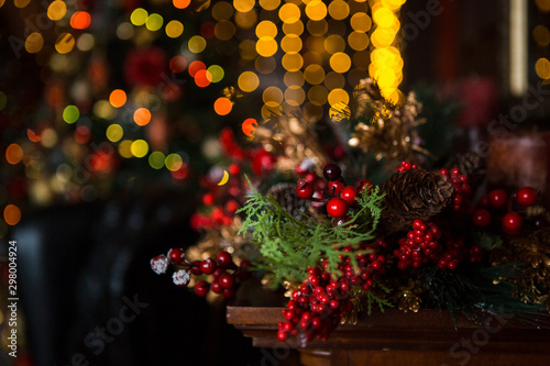 Fototapeta Christmas toys, garlands and interior elements in lights, home decoration for the holiday. Tied cinnamon sticks, kerosene lamp, glowing stars, lights in the side. obraz na płótnie