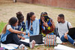 canvas print picture - Group of five african college students spending time together on campus at university yard. Black afro friends sitting on grass and studying with laptops.